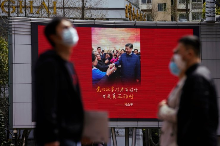 Pedestrians wearing face masks walk past a screen displaying an image of Chinese President Xi Jinping after the city's emergency alert level for coronavirus disease (COVID-19) was downgraded, in Shanghai, China, March 23, 2020. Reuters