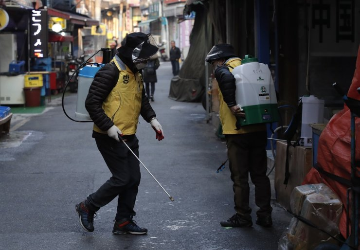 Workers prepare to disinfect as a precaution against the new coronavirus at a local market in Seoul, Wednesday. AP