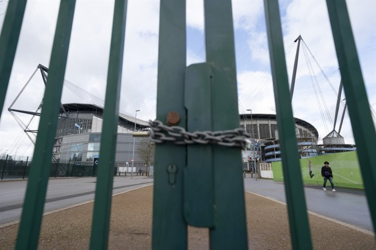 A locked gate is seen by the Etihad Stadium where Manchester City was due to play Burnley in an English Premier League soccer match Saturday, after all English soccer games were cancelled due to the spread of the COVID-19 Coronavirus. AP-Yonhap