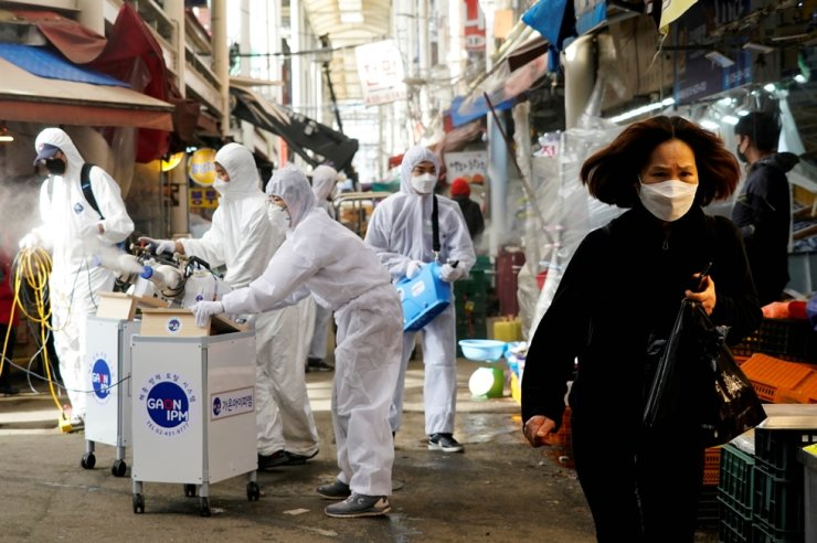 A woman wearing a mask to prevent contracting the coronavirus reacts as employees from a disinfection service company sanitize a traditional market in Seoul, Feb. 26, 2020. Reuters