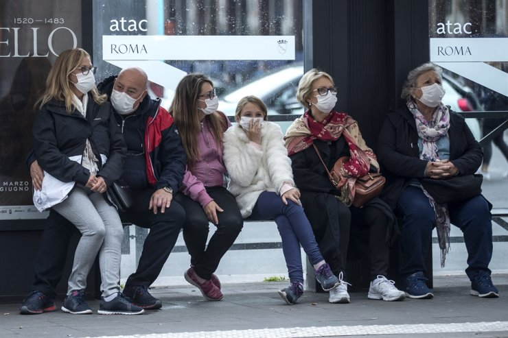 People wait at a bus stop, in Rome, Monday, March 9, 2020. Italy announced a sweeping quarantine early Sunday for its northern regions, igniting travel chaos as it restricted the movements of a quarter of its population in a bid to halt the new coronavirus' relentless march across Europe. AP