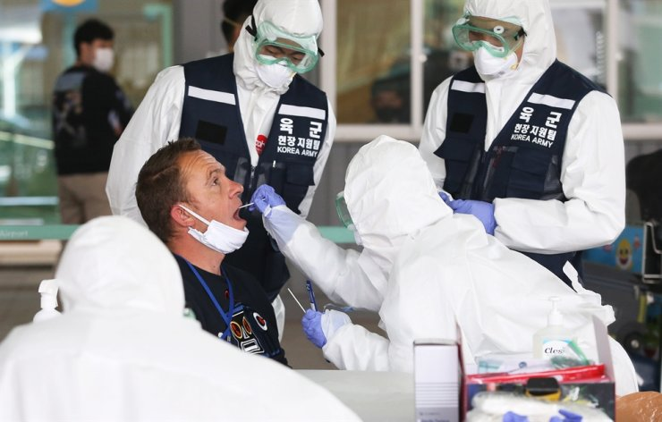 Medical workers wearing protective gear take samples from a foreign visitor at an 'Open Walking-Thru' centre for COVID-19 tests at Incheon International Airport in Incheon, Korea, March 27, 2020. EPA