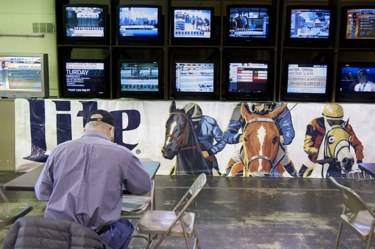 A person waits for the horses to race at Fonner Park in Grand Island, Neb., Saturday. Fonner was one of the few sporting venues in the country open to fans Saturday, unfortunately the races were called off due to dangerous track conditions following snowfall. AP-Yonhap