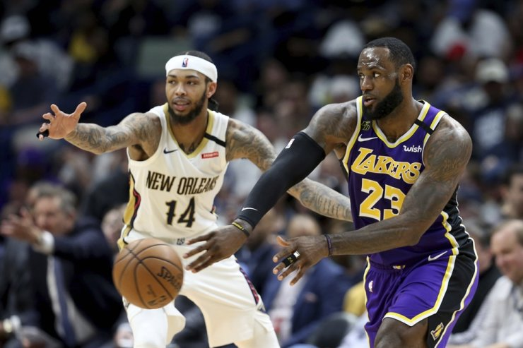 Los Angeles Lakers forward LeBron James, right, passes the ball in front of New Orleans Pelicans forward Brandon Ingram in the second half of an NBA basketball game in New Orleans in this March 1 file photo. James has been self-isolating at home for the last two weeks, part of the process his team had to go through after two players tested positive for the coronavirus. AP-Yonhap