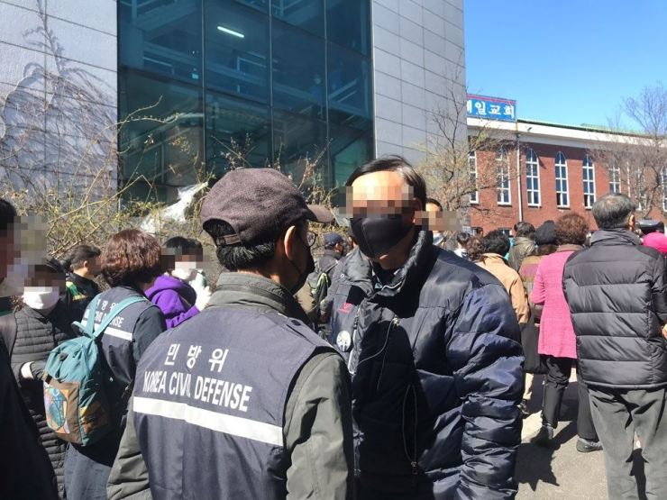 Churchgoers confront public officials trying to enter Sarang Jeil Church in Seoul on Sunday. The church held public services despite the government's strong request not to hold public gatherings at religious, indoor sports and recreational facilities as part of efforts to prevent the spread of coronavirus. Yonhap