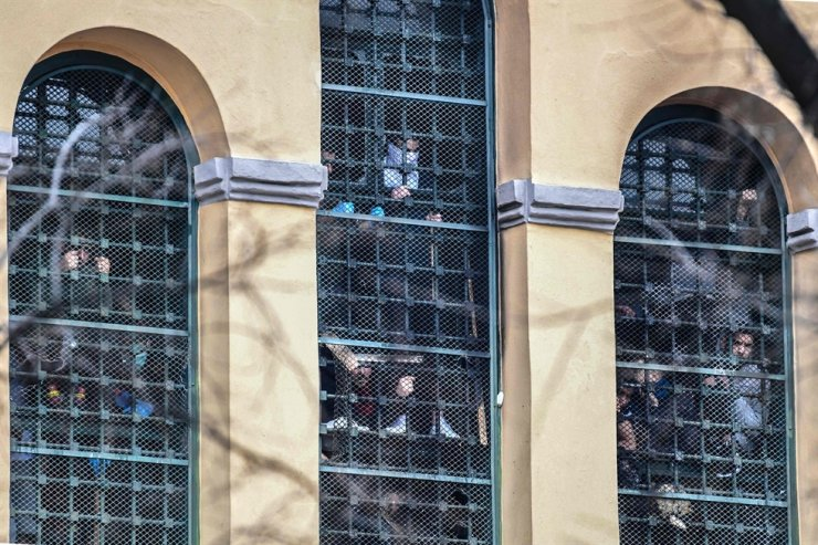 In this file photo taken on March 09, 2020 inmates hang on to bars behind windows of a wing as they stage a protest at the San Vittore prison in Milan, in one of Italy's quarantined red zones during the new coronavisurs crisis. AFP