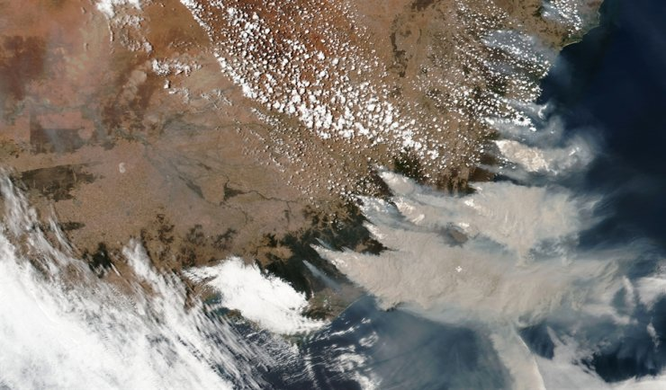 This satellite image provided by NASA, Jan. 4, shows wildfires in Victoria and New South Wales, Australia. Climate change raised the chances of Australia's extreme fire season by at least 30 percent, according to a study released Wednesday, by climate scientists at the World Weather Attribution group. / AP-Yonhap
