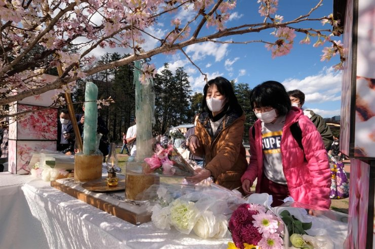 People offer flowers at an altar for victims of the 2011 earthquake and tsunami disaster at a memorial service in Tokyo on March 11, 2020 on the ninth anniversary. / AFP-Yonhap