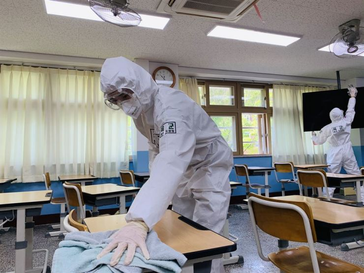 Soldiers disinfect a middle school in Daegu as part of efforts to help the city cope with the COVID-19 crisis, in this March 17 photo. /Yonhap