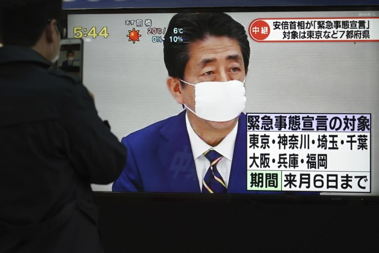 A pedestrian stops to watch a TV news as Japanese Prime Minister Shinzo Abe declares a state of emergency Tuesday, April 7, 2020, in Tokyo. Abe declared a state of emergency for Tokyo and six other prefectures to ramp up defenses against the spread of the coronavirus. (AP Photo/Eugene Hoshiko)