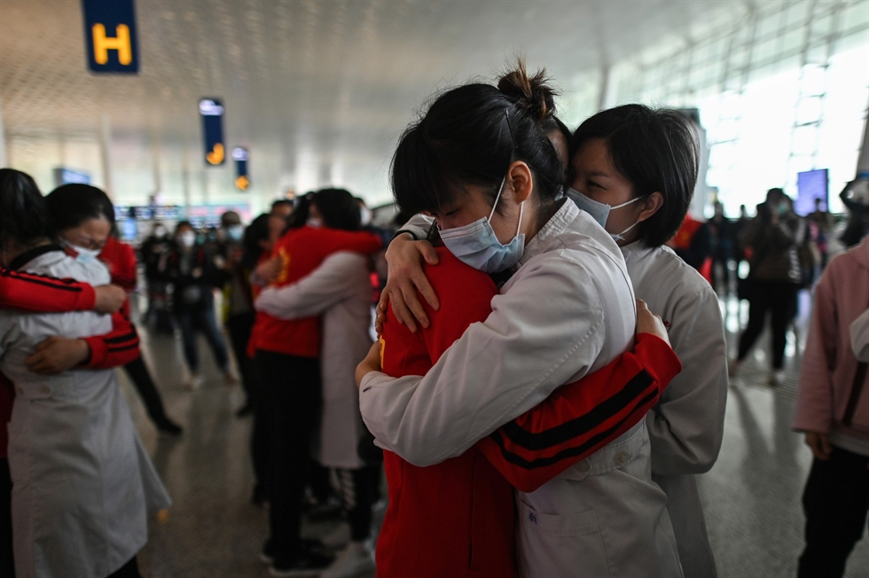 Medical workers hug at the Wuhan Tianhe International Airport after travel restrictions on leaving Wuhan, the capital of Hubei Province and China's epicenter of the COVID-19 outbreak, were lifted on April 8. Reuters