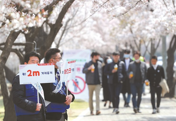 Officials from Yeongdeungpo-gu Office hold signs near Yeouinaru Station in Seoul, Monday, calling for people to keep a distance of two meters from one another, while citizens walk along and view the cherry blossoms. Yonhap
