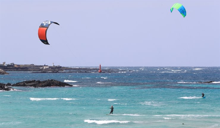 Kiteboarders play in the waves in the waters off Hamdeok Beach on Jeju Island, Tuesday. / Yonhap