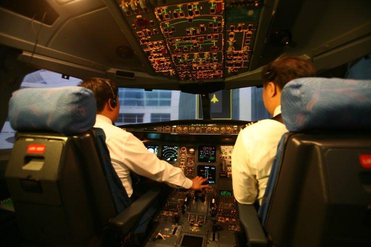 A Korean Air pilot hands control sticks, while a co-pilot looks on. / Courtesy of Korean Air