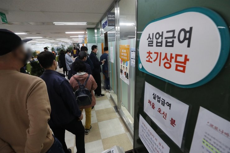 People line up in front of an office run by the Ministry of Employment and Labor in Seoul, Monday, to apply for unemployment benefits. The amount of state allowances paid to those unemployed or seeking jobs soared to a record high in March due mainly to the negative economic impact from the COVID-19 pandemic. /Yonhap