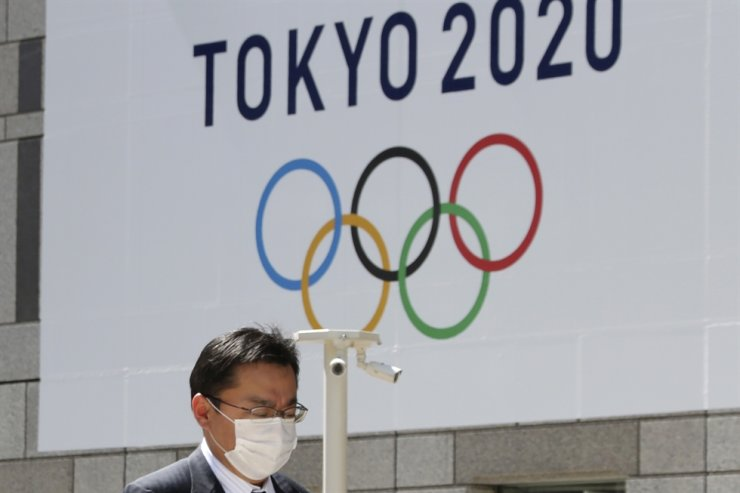 In this Wednesday, March 25, 2020, file photo, a man walks in front of a Tokyo Olympics logo at the Tokyo metropolitan government headquarters. The postponement of the Tokyo Games has catapulted the sports organizations that make up the backbone of the U.S. Olympic team into crisis. /AP