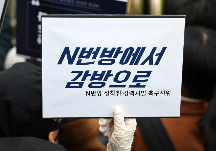 A protester holds up a sign that reads 'From Nth Room to Prison' at Jongno Police Station in Seoul, March 25, as Cho Ju-bin, the primary suspect in the infamous sexual-abuse case, is taken to a nearby police van. Korea Times photo by Koh Young-kwon