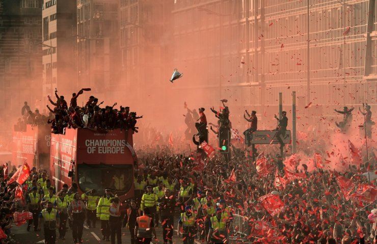 Football fans line the streets to see the Liverpool football team take part in an open-top bus parade around Liverpool, north-west England after winning the UEFA Champions League final football match between Liverpool and Tottenham, June 2. / AFP-Yonhap