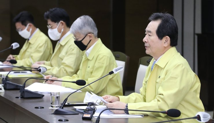 Prime Minister Chung Sye-kyun, right, speaks during a daily meeting on COVID-19 in Sejong city, Tuesday. The government said it's considering introducing electronic tagging wristbands for people under self-quarantine. /Yonhap