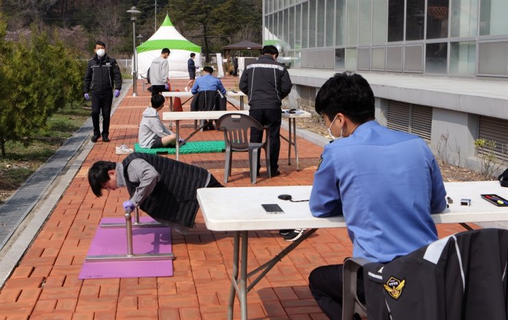 Human resources officials from the East Sea Coast Guard test applicants' physical strength during a recruitment process in Donghae, Gangwon Province, Tuesday. The examination usually takes place indoors but was moved outdoors this year due to the coronavirus pandemic. /Yonhap