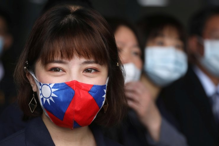 A staff member wears a face mask with a Taiwanese flag design, as protection due to the coronavirus disease (COVID-19) outbreak, at a factory for non woven filter fabric used to make surgical face masks, in Taoyuan, Taiwan, March 30, 2020. Reuters