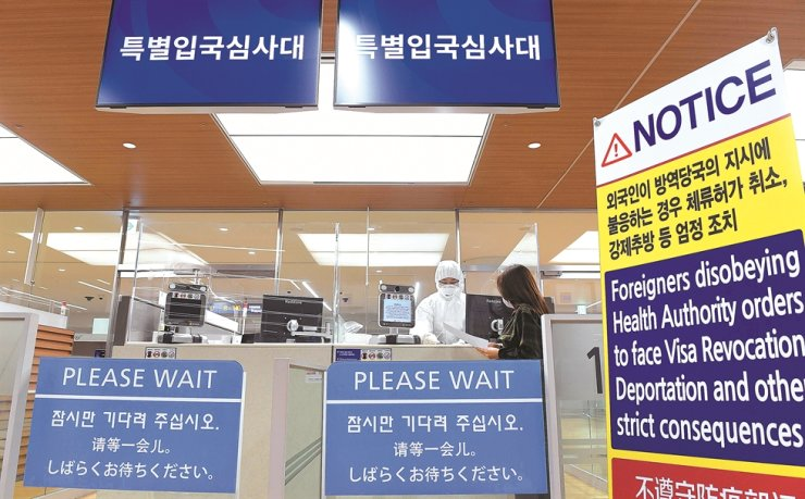 An immigration officer wearing anti-contamination clothing screens a traveler for symptoms of COVID-19 at a checkpoint in Incheon International Airport, Wednesday. Korea Times photo by Shim Hyun-chul