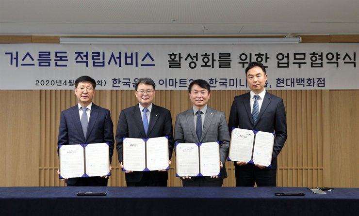 Bank of Korea (BOK) Deputy Governor Yoon Myun-shik, second from left, holds a copy of a memorandum of understanding with executives of three retail firms at the BOK headquarters in Seoul, Tuesday. The retailers agreed to allow customers to deposit any change left from cash purchases directly into their bank accounts, part of the BOK's move to create a cashless society. From left are Emart24 CEO Kim Song-yong, Yoon, Ministop Korea CEO Shim Kwan-sup and Hyundai Department Store Vice President Jung Ji-young. / Courtesy of BOK