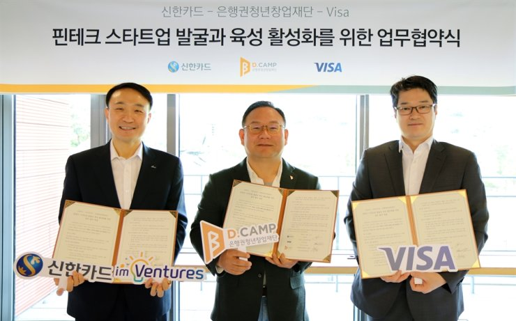 Shinhan Card's head of management planning Moon Dong-kwon, left, poses with chief of D.Camp Kim Hong-il, center, and Visa Korea Vice President Lee Yoo-jin, after the three parties signed an agreement to help foster fintech startups, at D.Camp in southern Seoul, Wednesday. D.Camp is a foundation that offers working space for startups and connects them to investors. Courtesy of Shinhan Card