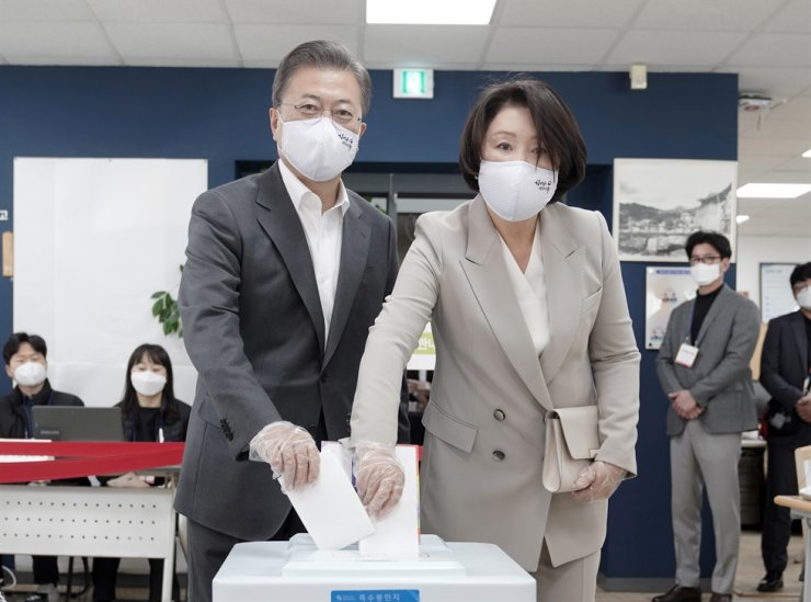 President Moon Jae-in and first lady Kim Jung-sook cast ballots at the Samcheong-dong Community Service Center in Seoul near Cheong Wa Dae, Friday, the first day of early voting for the April 15 general election. They wore face masks and protective gloves as part of measures taken at polling stations to prevent the spread of the COVID-19 pandemic. / Yonhap