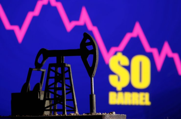 A 3D-printed oil pump jack is seen in front of a displayed stock graph and '$0 Barrel' words in this illustration picture, April 20, 2020. Reuters