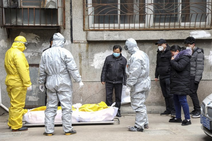 In this Feb. 1, 2020, file photo, funeral home workers remove the body of a person suspected to have died from the coronavirus outbreak from a residential building in Wuhan in central China's Hubei Province. AP