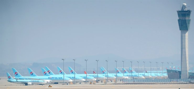 Korean Air planes stand at the parking ramp of Incheon International Airport, March 24, as air travel demand has declined sharply following the outbreak of COVID-19. / Yonhap