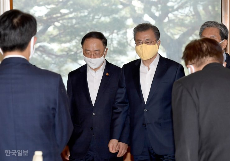 President Moon Jae-in, third from left, and Finance Minister Hong Nam-ki, second from left, enter a meeting room in Cheong Wa Dae, March 18, to attend a meeting convened to discuss measures to contain the COVID-19 pandemic. / Korea Times photo by Wang Tae-seok