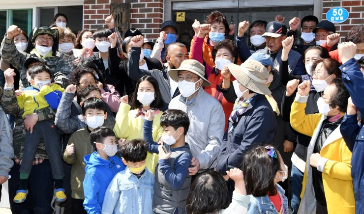 President Moon Jae-in takes a photo with citizens after planting pine trees in a reforestation area in Gangneung, Gangwon Province, on Arbor Day, Sunday. Yonhap