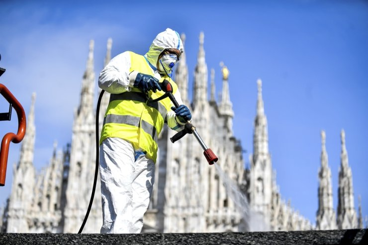 A worker sprays disinfectant to sanitize Duomo square, as Milan's main landmark, the gothic cathedral, stands out in the background, March 31. AP
