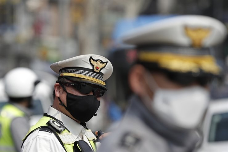South Korean police officers wearing face masks stand on duty during a campaign for the 2020 South Korean National Assembly election in Seoul, Tuesday, April 7, 2020. AP