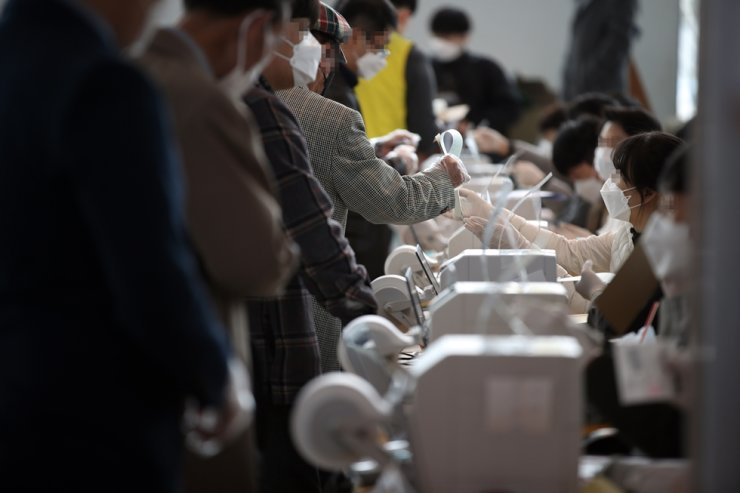 Voters wait for their turn to cast their ballots at a polling station near Seoul Station in central Seoul, Saturday. Yonhap