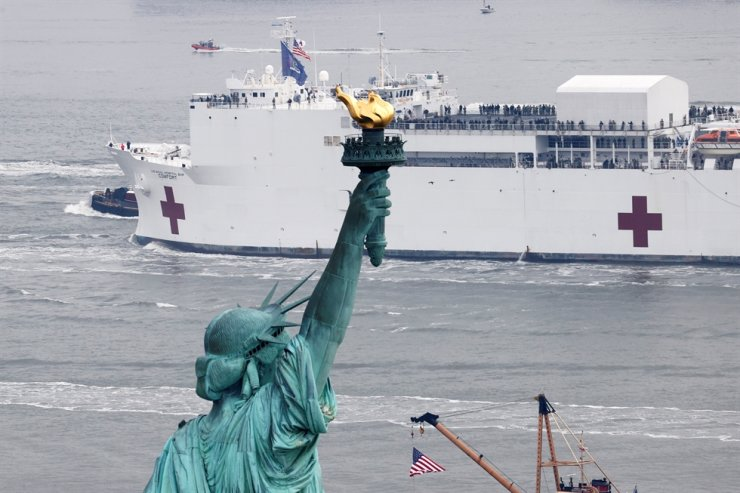 The USNS Comfort passes the Statue of Liberty as it enters New York Harbor during the outbreak of the coronavirus disease (COVID-19) in New York City, U.S., March 30, 2020. /REUTERS