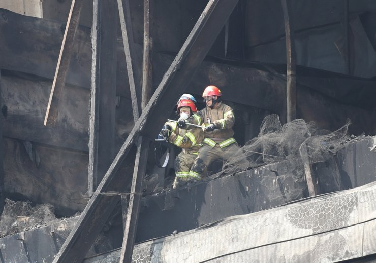 Firefighters remove debris from a fire-hit warehouse in Icheon, Gyeonggi Province, Thursday. The fire engulfed the four-story building under construction a day earlier, claiming 38 lives. Yonhap