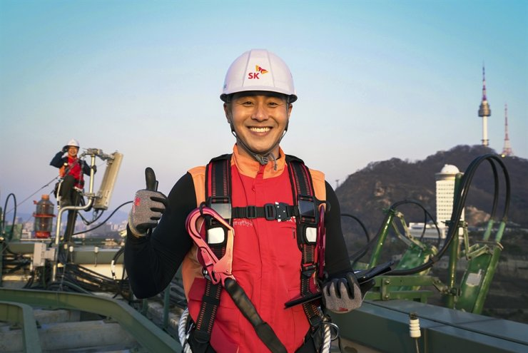 SKT employees gives a thumbs up while installing a 5G base station on top of a building in Seoul. Courtesy of SKT
