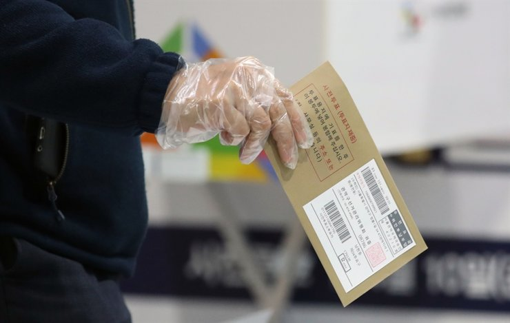 A voter wearing a protective glove casts his ballot at a polling station near Seoul Station in central Seoul, Friday. Yonhap