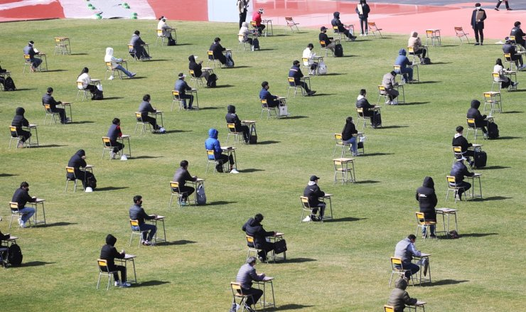 Applicants take a written test ― part of the recruitment process of Ansan Urban Corp. ― at a football stadium in Ansan, Gyeonggi Province, Saturday. The city-run company held an outdoor test to prevent the spread of COVID-19. / Yonhap