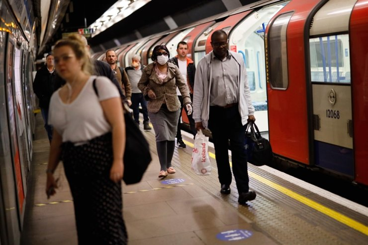Commuters walk along the platform at a tube station in London on April 22, 2020, as Britain remains under lockdown during the COVID-19 pandemic. AFP