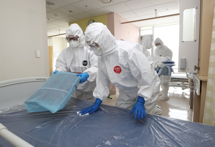 Staffers at a hospital in Daegu clean a ward, Friday, after COVID-19 patients who had been hospitalized there were discharged from the hospital. The city that was once considered the local epicenter of the virus outbreak reported no new cases for the first time in 52 days. / Yonhap