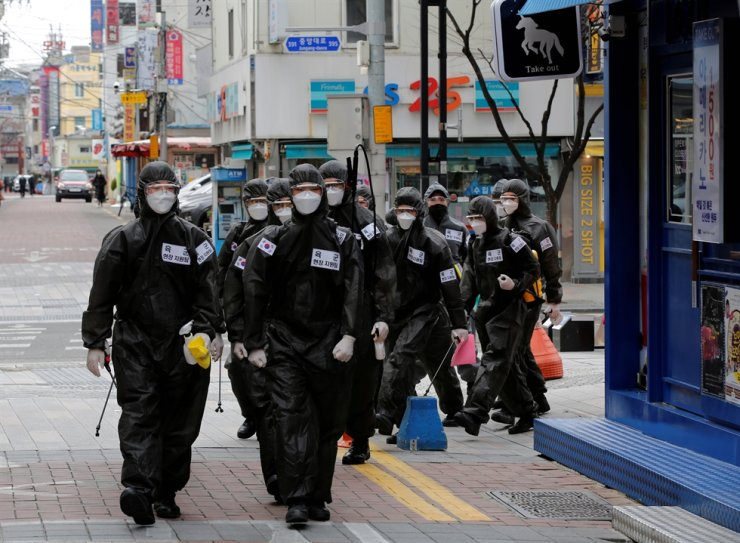Korean soldiers in protective gear make their way while they disinfect buildings downtown, following the rise in confirmed cases of COVID-19 in Daegu, Korea, March 15, 2020. Reuters