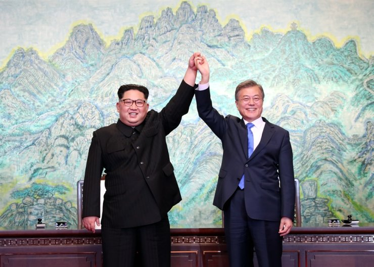 President Moon Jae-in and North Korean leader Kim Jong-un hold hands after signing a joint statement during their summit at the truce village of Panmunjeom, April 27, 2018. / Korea Times file