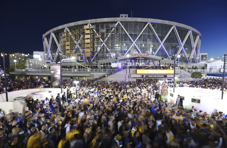 Golden State Warriors fans celebrate outside Oracle Arena in Oakland, Calif, June 8, 2018. With the distinct possibility of pro sports resuming in empty venues, a recent poll suggests a majority of U.S. fans wouldn't feel safe attending games anyway without a coronavirus vaccine. / AP-Yonhap