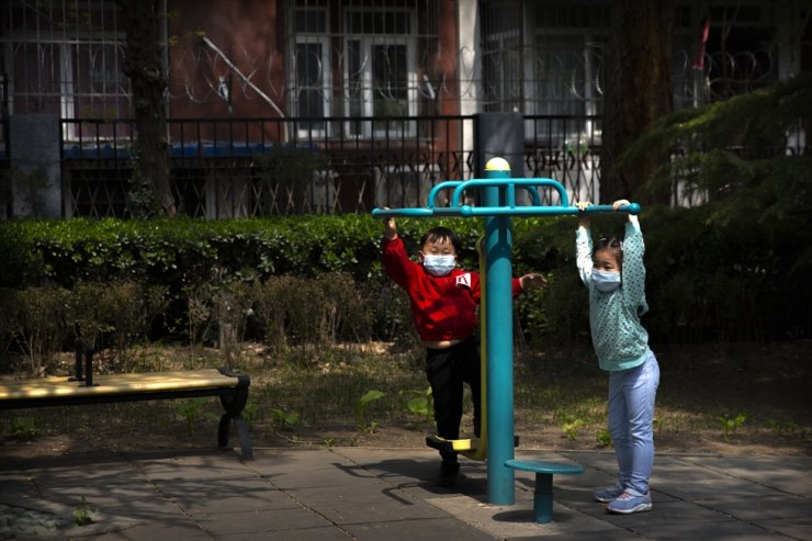 Children wear face masks as they play on gym equipment at a park in Beijing, Tuesday, April 7, 2020. AP