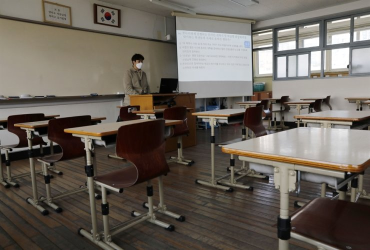 A teacher gives a class online from an empty classroom of Seoul Girls' High School in Seoul, Thursday, as the country finally started the new school year for seniors in middle and high schools after delays due to the COVID-19 outbreak. /Korea Times photo by Shim Hyun-chul