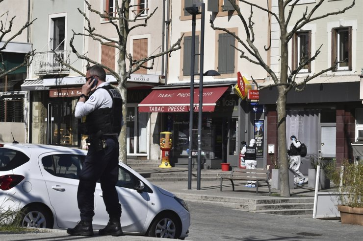A police officer gives a phone call after a man wielding a knife attacked residents venturing out to shop in the town under lockdown, Saturday, April 4, 2020, in Romans-sur-Isere, southern France. AP